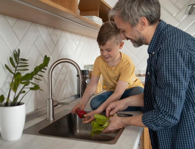Pai e filho lavando vegetais