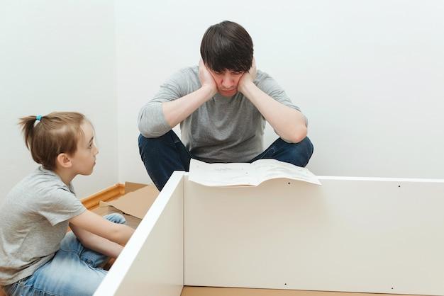 Pai e filho lendo instruções para montagem de móveis. pai e filho montando móveis em casa. montagem de móveis por conta própria. o pai ajuda o filho a montar uma estante.