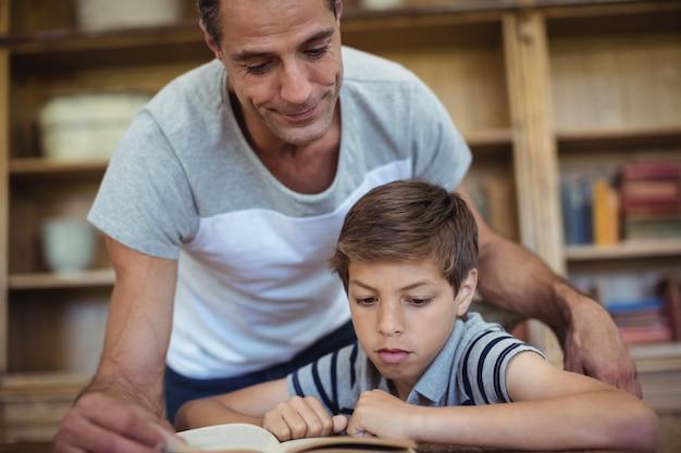 Pai e filho lendo um livro na sala de estudo