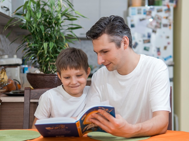 Pai e filho lendo um livro vista frontal