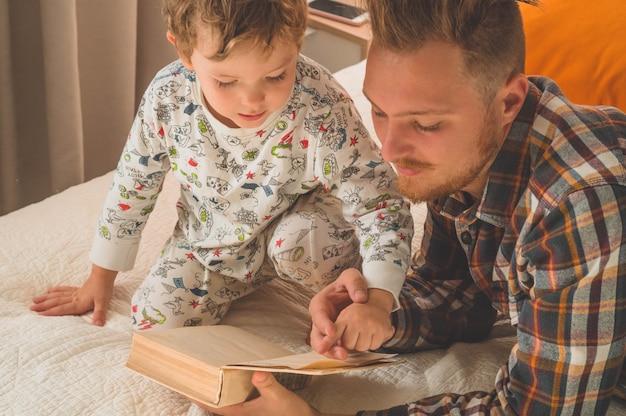 Pai e filho leram um livro juntos, sorrindo e se abraçando. férias em família e união