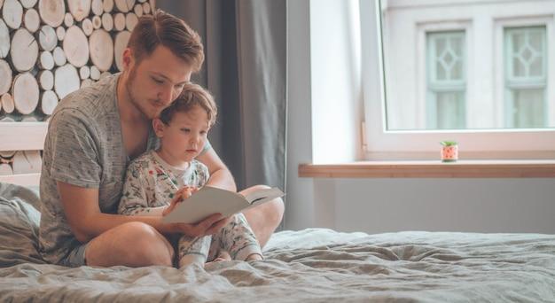 Pai e filho leram um livro juntos, sorrindo e se abraçando