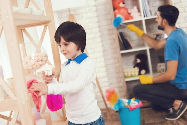 Pai e filho limpam superfícies de móveis de poeira