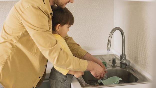 Pai e filho limpando os talheres e pratos
