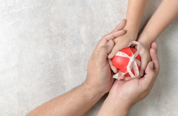 Pai e filho mãos segurando um coração vermelho