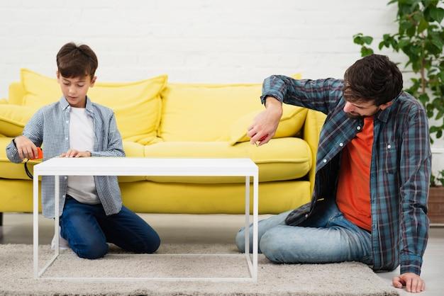 Pai e filho medindo uma mesa