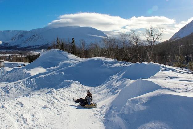 Pai e filho montam tubos de neve da montanha. diversão de inverno em um dia claro e gelado de neve. férias em família conjunta