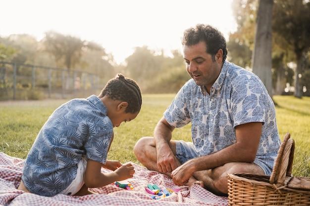 Pai e filho multirraciais se divertindo com brinquedos de madeira ao ar livre no parque da cidade - foco no rosto do pai