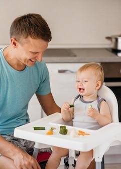 Pai e filho na cadeira alta comendo