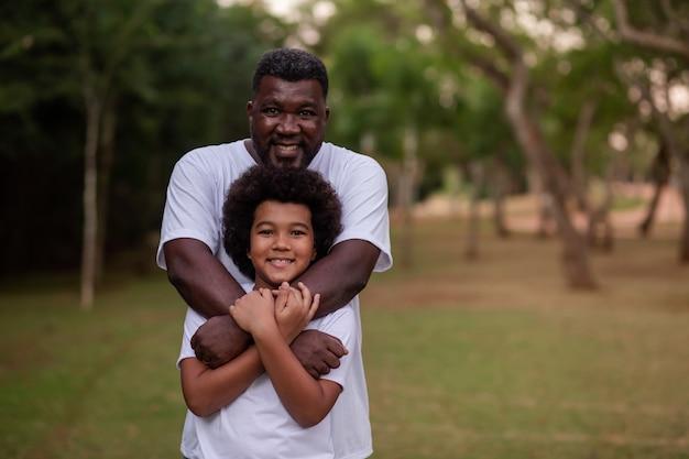 Pai e filho negros no parque se abraçando, sorrindo, olhando para a câmera