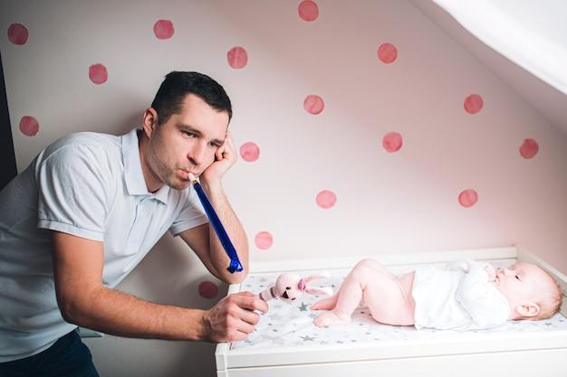 Pai e filho no berçário. o primeiro ano de vida. incerteza e medo de uma criança. papai não sabe o que fazer com a criança