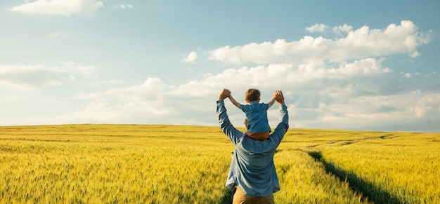 Pai e filho no campo de trigo, criança sentada nos ombros do pai