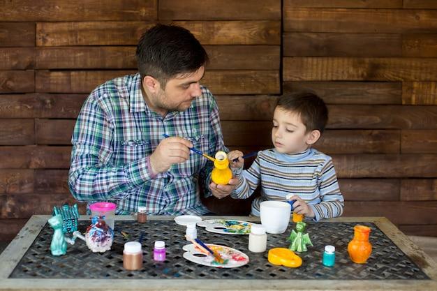 Pai e filho no estúdio de pintar um vaso.