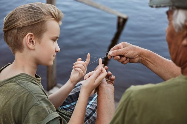 Pai e filho no pontão de madeira, pai ensinando seu filho a desembaraçar o nó na linha de pesca, a família a passar tempo juntos enquanto apanha peixes perto do lago.