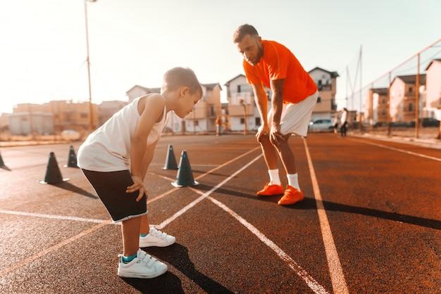 Pai e filho no sportswear, segurando as mãos nos joelhos e descansando após o exercício na quadra de manhã.