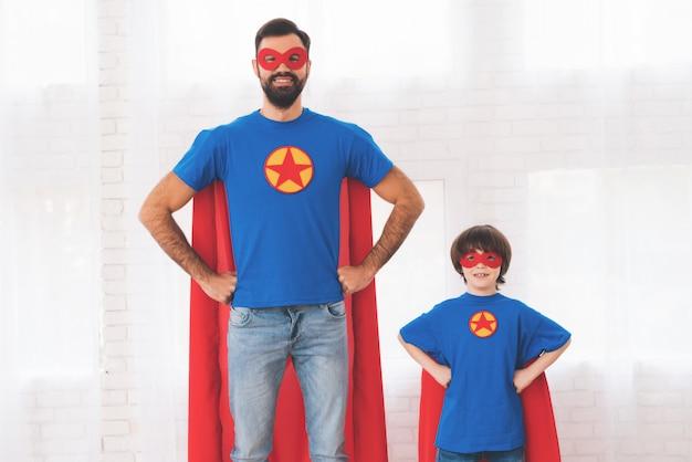 Pai e filho nos ternos vermelhos e azuis dos super-heróis.