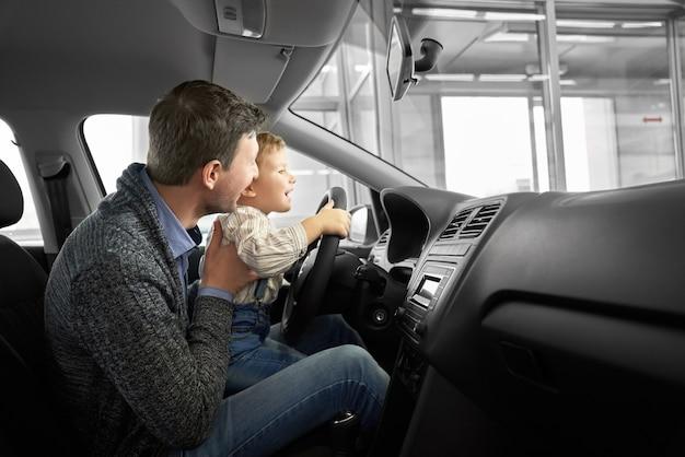 Pai e filho, observando a cabine de carro novo na concessionária.