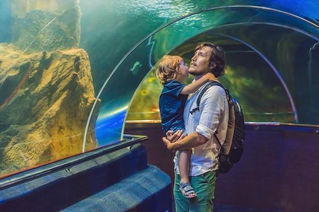 Pai e filho olham para os peixes no aquário no oceanário.