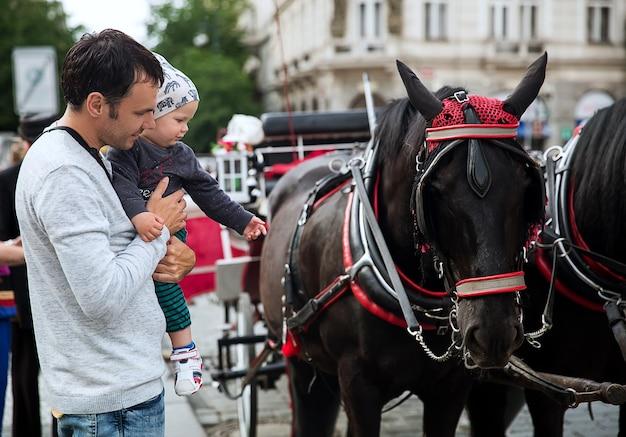 Pai e filho, olham para uma carruagem de cavalos na praça velha de praga, república tcheca
