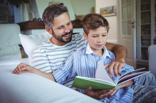 Pai e filho, olhando para o álbum de fotos na sala de estar