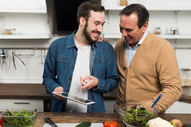 Pai e filho olhando tablet na cozinha