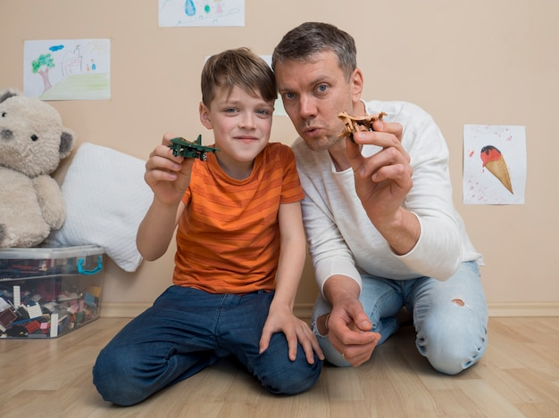 Pai e filho operam com brinquedos de avião