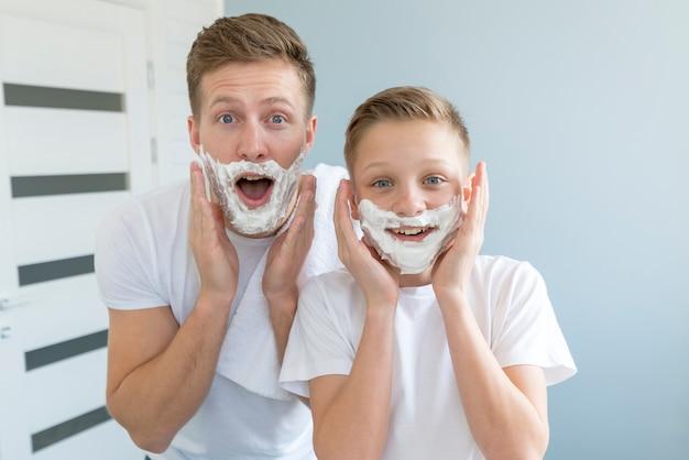 Pai e filho parecendo engraçado com espuma de barbear