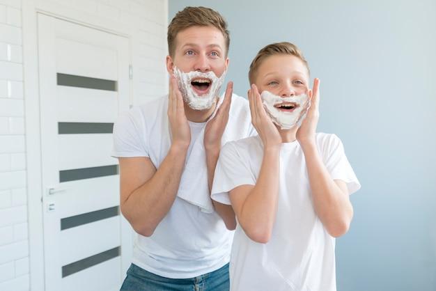 Pai e filho parecendo engraçado com gel de barbear