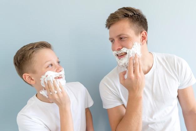Pai e filho parecidos com creme de barbear