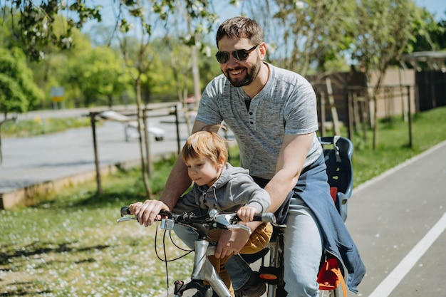 Pai e filho pedalando juntos em uma bicicleta ao longo da ciclovia. conceito do dia dos pais. imagem com foco seletivo. foto de alta qualidade