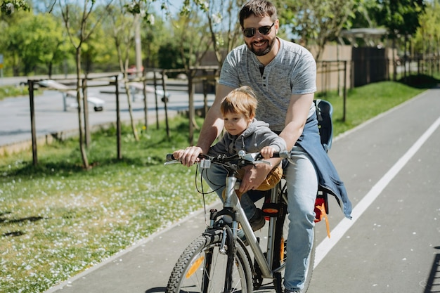 Pai e filho pedalando juntos em uma bicicleta