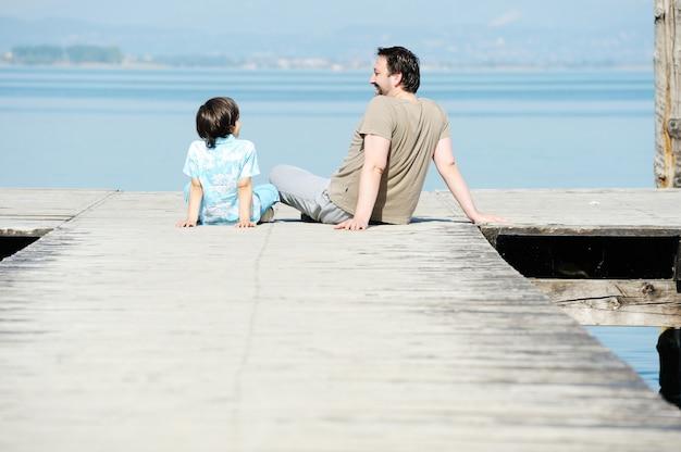 Pai e filho pela doca em um belo lago