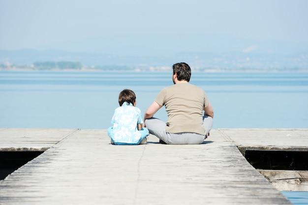 Pai e filho pela doca em um lindo lago