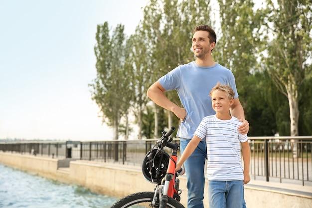 Pai e filho pequeno com bicicleta ao ar livre