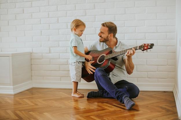 Pai e filho pequeno com guitarra