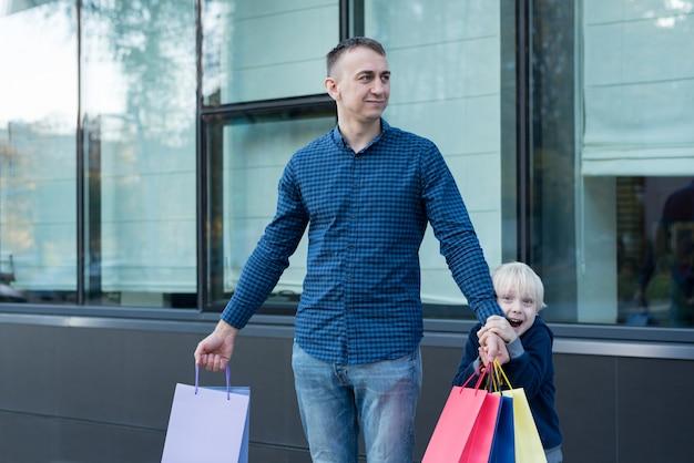 Pai e filho pequeno com sacolas coloridas na rua.