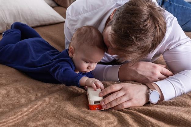 Pai e filho pequeno deitado na cama e brincando com o carrinho de brinquedo da minivan