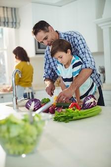 Pai e filho picar legumes na cozinha