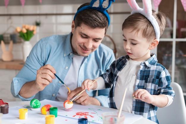 Pai e filho pintando ovos para a páscoa juntos