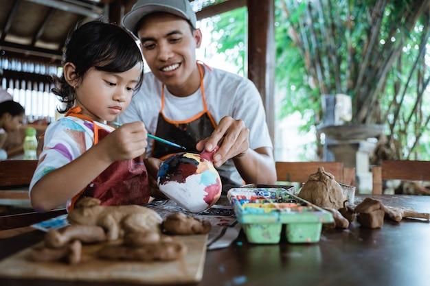 Pai e filho pintando produtos de cerâmica