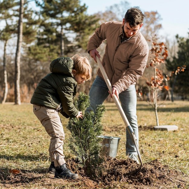 Pai e filho plantando uma árvore juntos