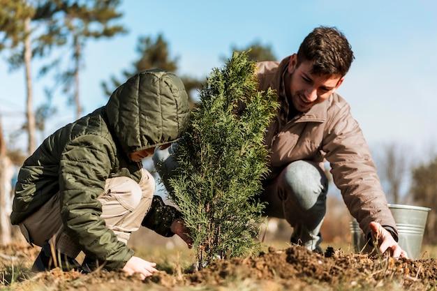 Pai e filho plantando uma árvore