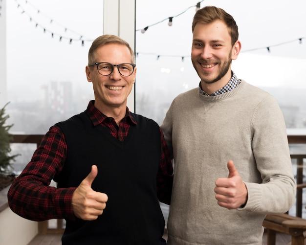 Pai e filho posando com polegares para cima