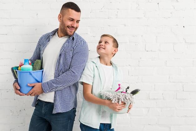 Pai e filho posando junto com produtos de limpeza