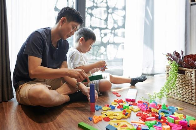 Pai e filho pré-adolescente sentados no chão em casa construindo torres com blocos de plástico