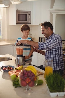 Pai e filho preparando batido na cozinha