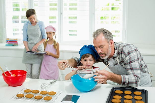 Pai e filho preparando biscoitos na cozinha