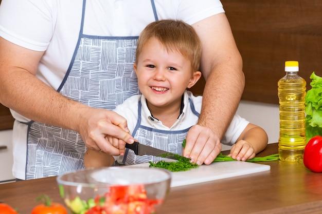 Pai e filho preparando salada na cozinha com legumes