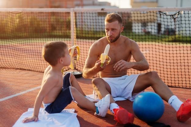 Pai e filho que comem banana após o treinamento exterior da manhã de verão.