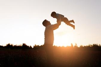 Pai e filho que jogam no parque no tempo do por do sol. Família feliz se divertindo ao ar livre